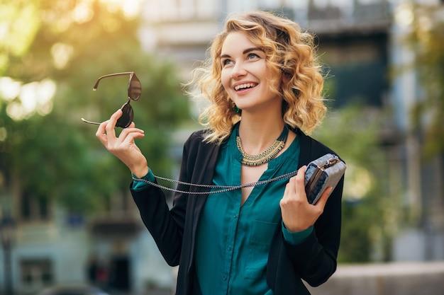 Elegante bella donna in jeans e giacca che cammina in strada con borsetta, stile elegante, tendenze della moda primaverile