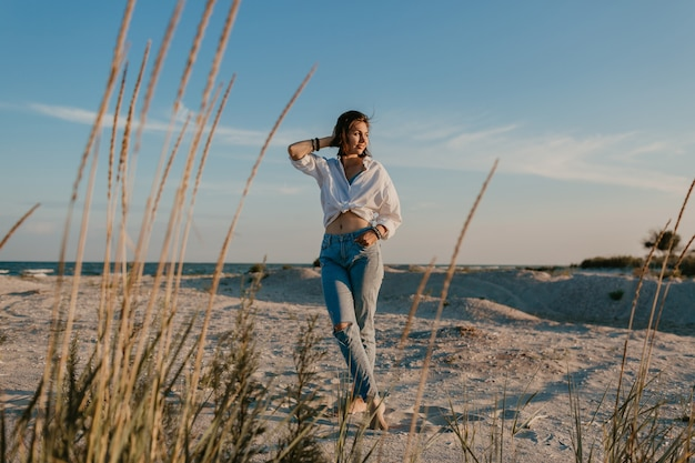 Стильная красивая женщина на летних каникулах на пляже, богемный стиль, джинсы