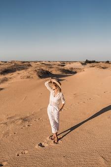 일몰에 밀짚 모자를 쓰고 흰 옷을 입고 사막 모래에서 걷는 세련된 아름다운 여자