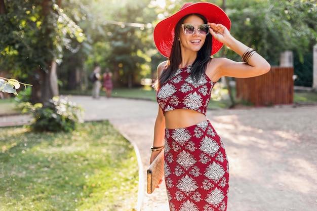 熱帯の衣装で公園を歩いているスタイリッシュな美しい女性。ストリートスタイルの夏のファッショントレンドの女性。わらのハンドバッグ、赤い帽子、サングラス、アクセサリーを身に着けています。休暇中に幸せな気分で笑っている女の子。
