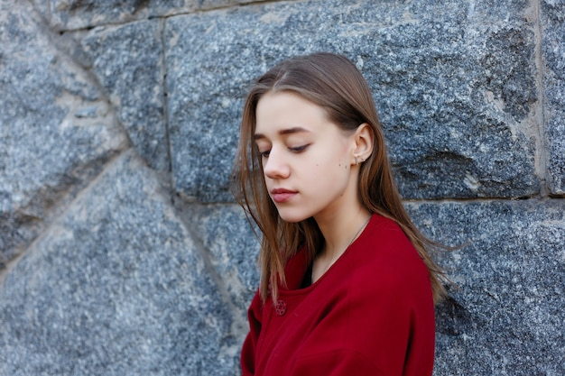 赤いコート、秋のファッショントレンドで通りを歩くスタイリッシュな美しい女性。ファッション秋の写真。女性のファッション。都市のライフスタイル。
