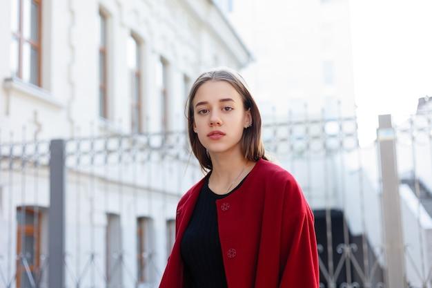 赤いコート、秋のファッショントレンドで通りを歩くスタイリッシュな美しい女性。