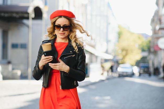Стильная красивая женщина гуляет по улице в красном платье, модная тенденция, держа в руке кофе в бумажном стаканчике