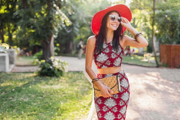 Stylish beautiful woman walking in park in tropical outfit. lady in street style summer fashion trend. wearing straw handbag, red hat, sunglasses, accessories. girl smiling in happy mood on vacation.