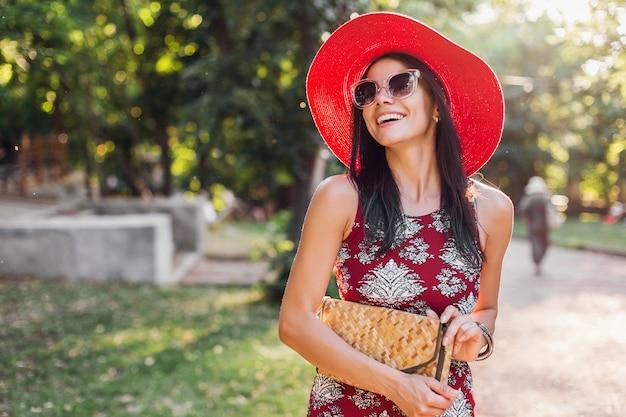Elegante bella donna che cammina nel parco in abito tropicale. signora nella tendenza della moda estiva street style. indossa una borsa di paglia, cappello rosso, occhiali da sole, accessori. ragazza sorridente di buon umore in vacanza.