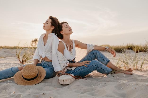 Стильные красивые женщины на летних каникулах на пляже, в богемном стиле, веселятся