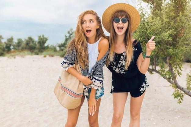 熱帯のビーチで夏休みにスタイリッシュな美しい女性、ボヘミアンスタイル、一緒に友達、ファッションアクセサリー、笑顔、幸せな感情、前向きな気分、ショートパンツ、麦わら帽子、楽しんで