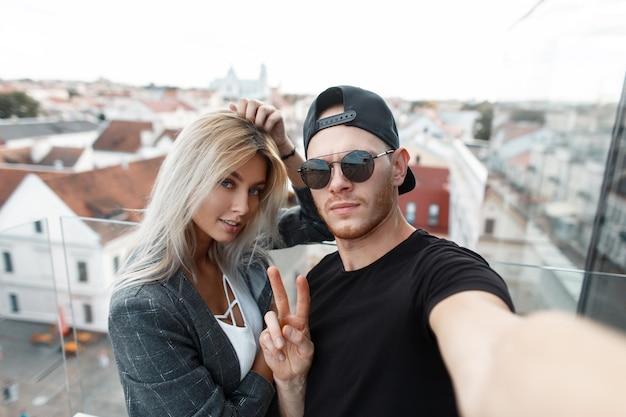街で自分撮りをしているスタイリッシュな美しい若いカップル。スタイリッシュな女性と一緒にファッショナブルな男性が旅行して写真を撮る