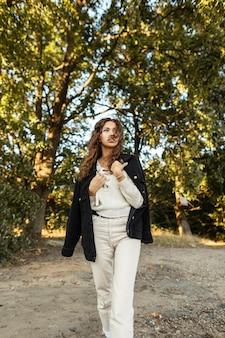 세련된 검은색 데님 재킷과 스웨터를 입은 세련된 아름다운 곱슬머리 모델 소녀가 공원을 산책합니다.