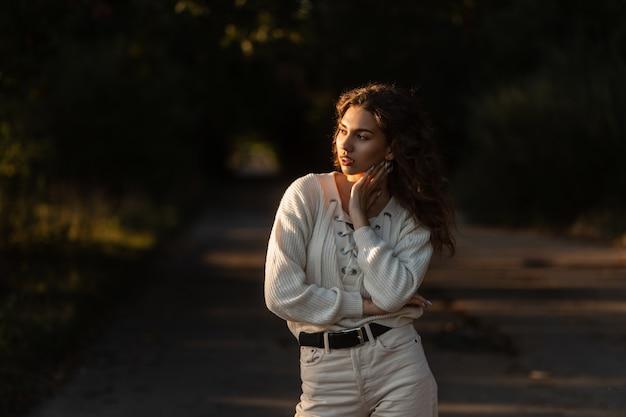 니트 옷을 입은 세련되고 아름다운 곱슬머리 모델 소녀가 해질녘 공원에서 산책합니다. 여성의 자연의 아름다움