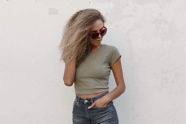 Стильная красивая молодая кудрявая женщина в розовых очках в винтажной джинсовой одежде и стильной футболке у белой стены