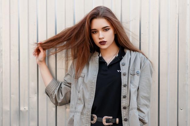 금속 벽 근처에 검은 폴로 셔츠와 유행 재킷에 세련된 아름다운 젊은 여성 모델