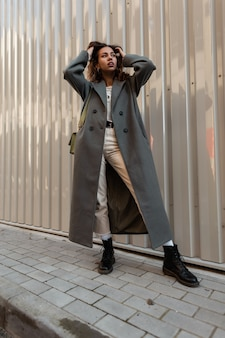 거리의 금속 벽 근처에서 포즈를 취한 핸드백과 신발이 있는 세련된 코트에 곱슬머리를 한 세련된 아름다운 소녀