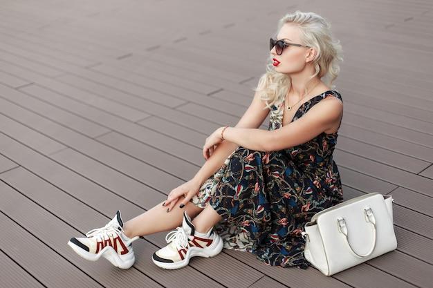 トレンディなドレスを着たサングラスとバッグとスニーカーのパターンを持つスタイリッシュな美しい少女は、木の床に座っています