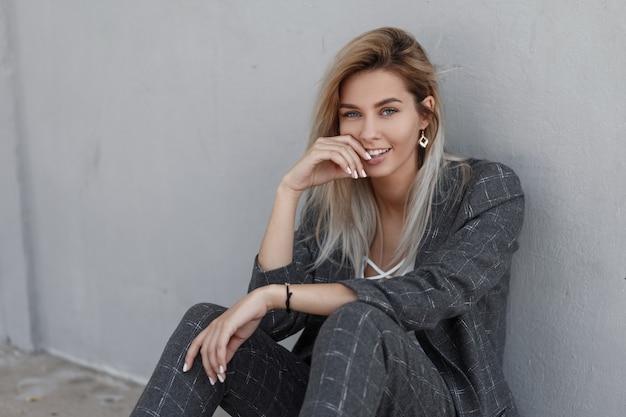 Стильная красивая молодая счастливая женщина с улыбкой в модном сером костюме и белой футболке сидит у стены на улице