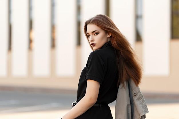야외에서 포즈를 취하는 긴 재킷과 검은 폴로에서 세련 된 아름 다운 젊은 모델 소녀