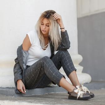 열 근처 거리에 앉아 신발 회색 정장에 세련 된 아름 다운 젊은 모델 여자 금발