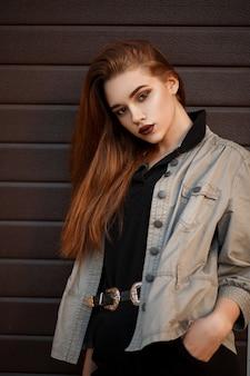 유행 재킷과 세련된 폴로에 세련된 아름다운 젊은 모델 여자가 거리의 게이트 근처에 서