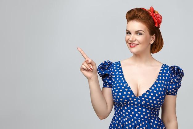 Elegante bella giovane donna dai capelli rossi che indossa rossetto rosso e vestito blu punteggiato sorridendo con gioia, indicando il dito indice al muro in bianco dello studio grigio con lo spazio della copia per il tuo contenuto promozionale