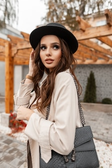 Stylish beautiful young woman in fashionable elegant clothes with a coat, hat and leather handbag walks in the city. glamorous feminine style and beauty