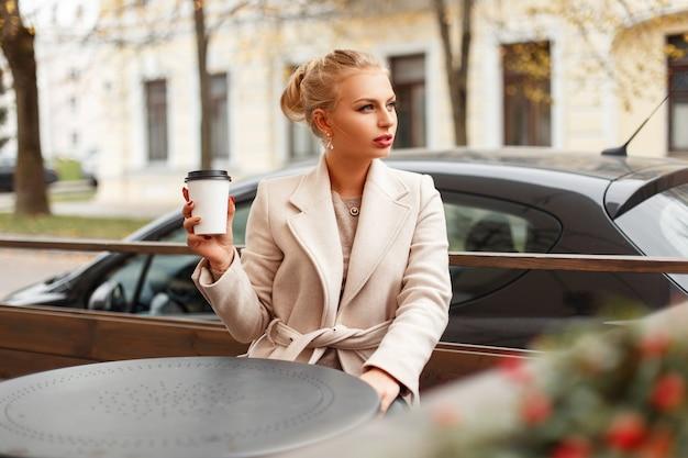 세련 된 아름 다운 젊은 여자 커피 한 잔을 들고 가을 날에 카페에서 휴식