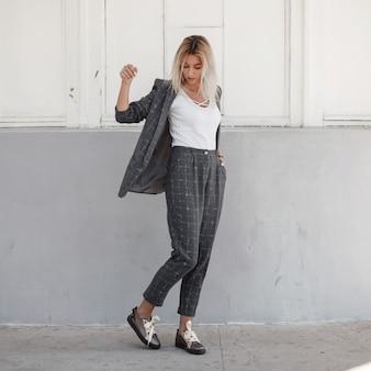 Стильная красивая молодая женщина в сером пиджаке с белой футболкой и серых модных брюках с туфлями позирует на улице. модная одежда в деловом стиле