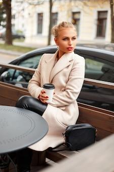 테라스에 앉아 커피와 트렌디 한 코트에 세련 된 아름 다운 젊은 여자