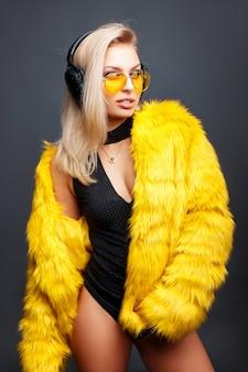 Стильная красивая молодая женщина в желтых солнцезащитных очках и желтой шубе, слушая музыку на сером.