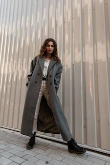 도시의 금속 벽 근처에 부츠가 달린 세련된 긴 코트에 곱슬머리를 한 세련된 아름다운 젊은 여성 모델. 캐주얼한 여성스러운 스타일