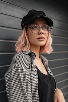 黒のtシャツの格子縞のシャツとファッションカジュアルな服装でかわいい顔を持つスタイリッシュな美しい若い女性は通りの灰色の門の近くに立っています