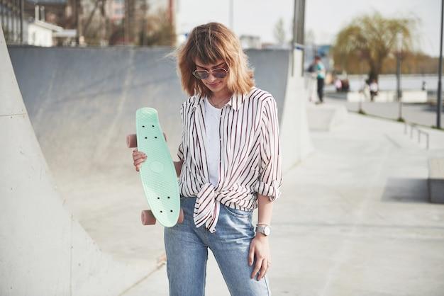 Стильная красивая молодая женщина со скейтбордом, в прекрасный летний солнечный день.