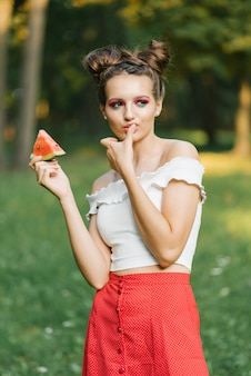 Stylish beautiful young woman with bright juicy makeup in the form of a watermelon holds a piece of watermelon in her hand and tastes it