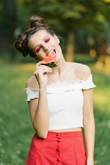 Stylish beautiful young woman with bright juicy makeup in the form of a watermelon holds a piece of watermelon
