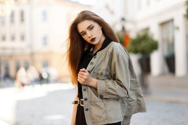 도시에서 야외에서 걷는 검은 티셔츠와 세련된 재킷에 어두운 입술을 가진 세련된 아름다운 젊은 여자