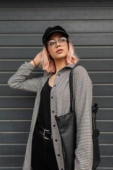 通りの灰色の門の近くでポーズをとるバッグとファッショナブルな格子縞のシャツのメガネとヴィンテージのキャップを持つスタイリッシュな美しい若い女性