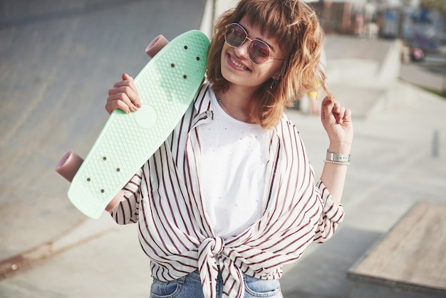 Elegante bella giovane donna con uno skateboard, in una bella giornata di sole estivo.