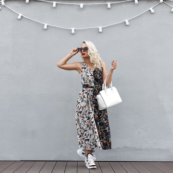 회색 벽 근처 유행 드레스에 선글라스와 세련 된 아름 다운 젊은 여자