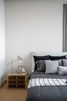 Stylish bedroom corner with leather headboard and bed with soft pillows setting with white painted wall on the background / cozy interior design / modern interior