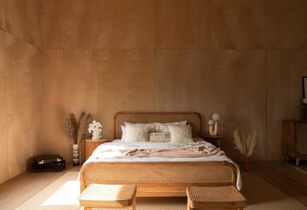 Стильный уголок спальни с изголовьем из ротанга и кроватью с мягкими белыми подушками и фанерной стеной.
