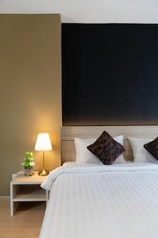ネイビーブルーと黄色の塗られた壁と木製のヘッドボードの柔らかい枕設定でスタイリッシュな寝室のコーナー