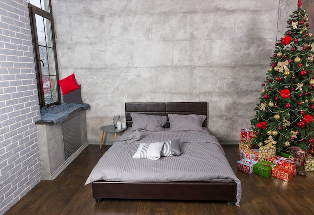 灰色のロフトスタイルのスタイリッシュなベッドルームとプレゼント付きのクリスマスツリー、灰色の毛布付きのベッド