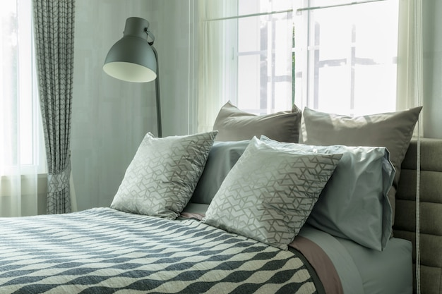 Stylish bedroom interior design with patterned pillows on bed and decorative table lamp.