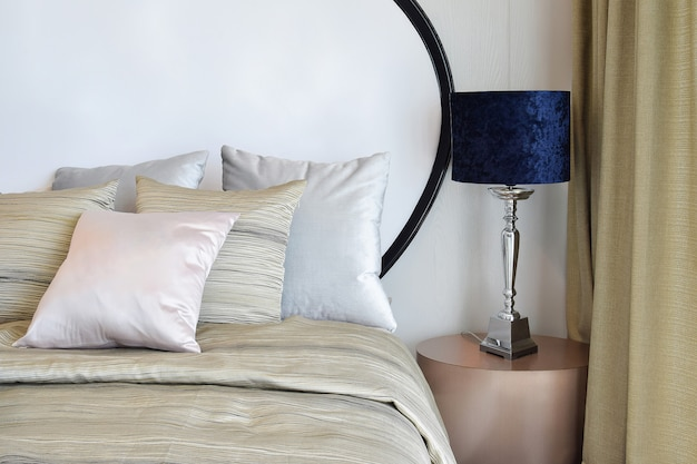 Stylish bedroom interior design with pillows on bed and decorative table lamp.