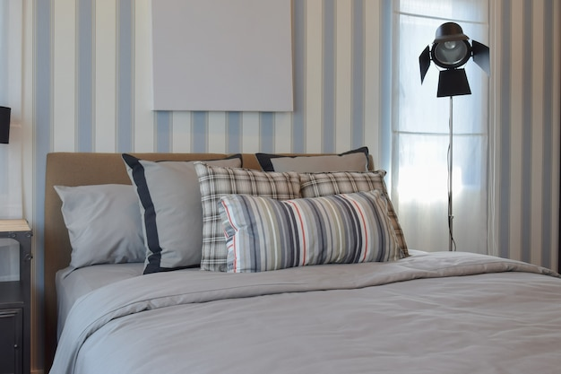 Stylish bedroom interior design with striped pillows on bed