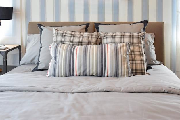 Стильный дизайн интерьера спальни с полосатыми подушками на кровати и декоративной настольной лампой.