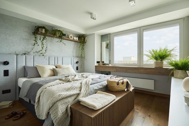 작은 침대, 나무 가슴, 가정 정원, 흰색 침구, 베개 및 담요가 있는 현대적인 아파트의 세련된 침실 인테리어. 회색 벽과 갈색 나무 쪽모이 세공 마루가 있는 밝은 공간. 주형