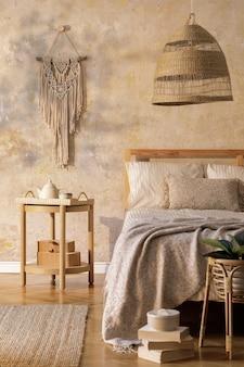 디자인 커피 테이블, 가구, 카펫, 등나무 장식, 마크라메 및 우아한 개인 액세서리가있는 세련된 침실 인테리어. 아름다운 베이지 침대 시트, 담요 및 베개. 주형.