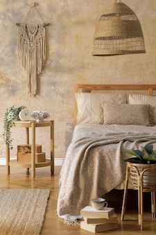 Стильный интерьер спальни с дизайнерским журнальным столиком, мебелью, ковром, декором из ротанга, макраме и элегантными личными аксессуарами. красивые бежевые простыни, одеяло и подушки. шаблон.