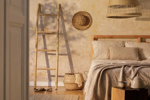디자인 커피 테이블, 가구, 사다리, 카펫, 등나무 장식 및 우아한 개인 액세서리를 갖춘 세련된 침실 인테리어. 아름다운 베이지 색 침대 시트, 담요 및 베개 ..