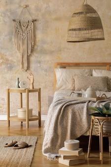 デザインのコーヒー テーブル、家具、植物、カーペット、籐の装飾、エレガントな個人用アクセサリーを備えたスタイリッシュな寝室のインテリア。美しいベージュのベッド シーツ、毛布、枕。